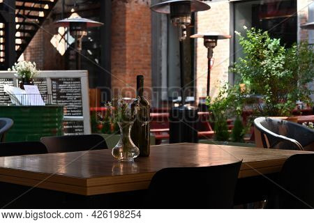 A Wooden Table On The Terrace Outside The Cafe, In The Courtyard, Is Decorated With A Bouquet Of Dai