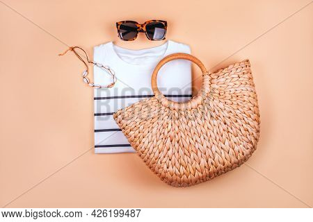 Summer Fashion Flatlay With White Striped T-shirt, Straw Summer Bag, Shell Necklace And Tortoiseshel