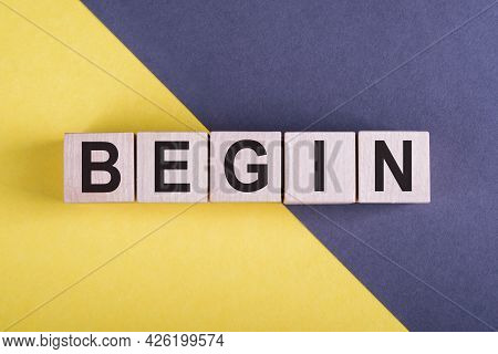 Word Begin On Wooden Cubes On Yellow - Gray Background.