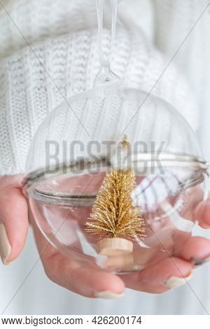 Woman holding a glass bauble with gold Christmas tree inside