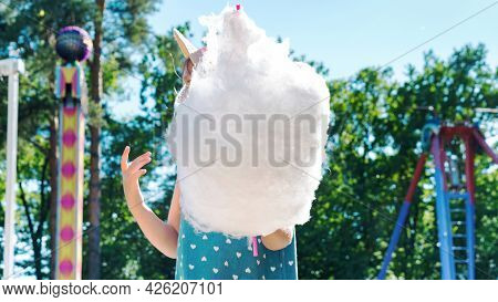 A Kid Eats A Huge Amount Of Cotton Candy At An Amusement Park In Summer. Happy Carefree Childhood Co
