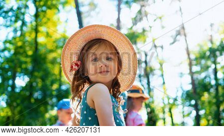 Portrait Of A Beautiful Little Girl In A Hat. A Cute Girl Is Walking In The Park With Kids On Vacati
