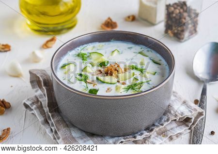 Traditional Bulgarian Cold Soup Tarator With Cucumber, Herbs And Walnuts In A Gray Bowl On A Light C