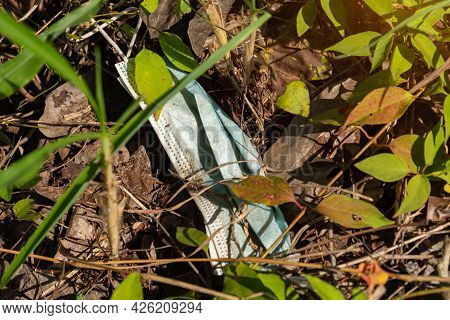 An Used Medical Mask Dumping On The Ground. Coronavirus,covid-19 And Environmental Pollution Concept
