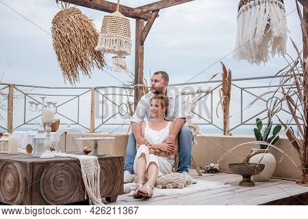 Loving Happy Middle-aged Couple In White Sitting On The Floor On The Open Terrace Of The Roof Overlo