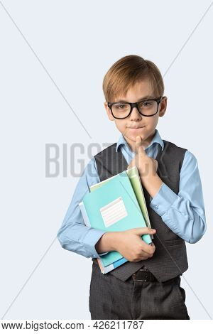 Caucasian Boy In A School Uniform Holds A Notebook In Him Hands. A Child With Glasses. Emotions On T