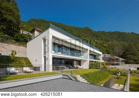 Modern house of two apartments with a beautiful garden directly on Lake Ceresio. Sunny day with blue sky. Minimalist and linear architecture. Panoramic view in background of green hills during summer.