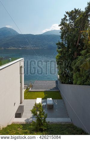 Modern house with direct access to the lake. Two chaise lounges for some relaxation on a beautiful sunny summer day. Nature is green and the lake is calm. Panoramic view
