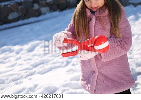 Cute Little Girl Playing With Snowball Maker Outdoors, Closeup