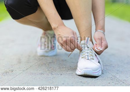 Girl Runner Tying The Laces, Shoelace, On Sneakers, Shoes On Treadmill Running In Summer Park. Woman