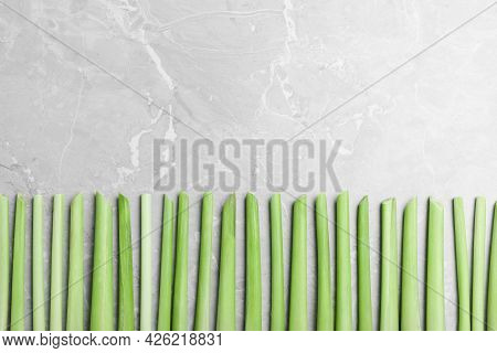 Fresh Lemongrass Stalks On Light Grey Marble Table, Flat Lay. Space For Text