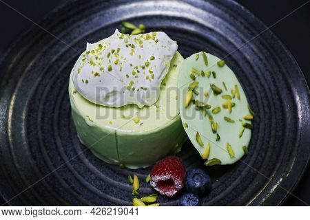 Cheesecake With Pistachio Flavor, Decorated With Berries And Fresh Cream