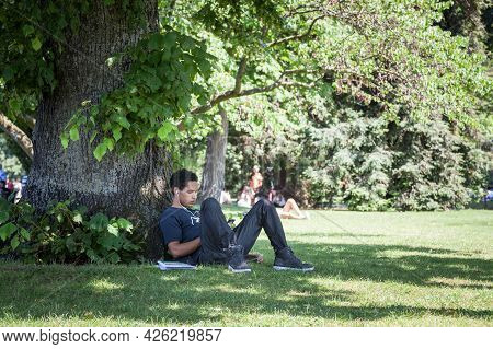 Geneva, Switzerland - June 19, 2017: Young Adult, Student, Relaxing Listening To Music After Studyin