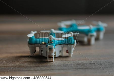 View Of Tiny Drone On A Wooden Background. Small Blue Drone With White Propellers.