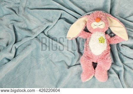 A Plush Bunny Toy Sitting On Plush Blanket And White Wall. Plush Pink Bunny Toy With Pink Knitted Oc