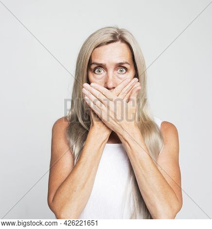 Secret and emotion concept. Portrait of beautiful nice shocked gray-haired old woman covering her mouth with palms. Isolated over light grey background.