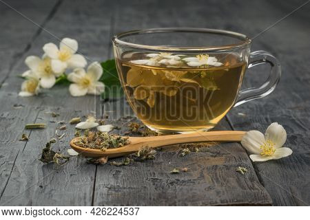 A Cup Of Flower Tea And A Wooden Spoon With Dried Herbs. An Invigorating Drink That Is Good For Your