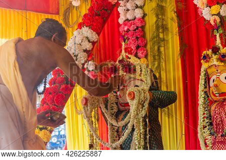 Howrah, West Bengal, India - 29th June 2020 : Hindu Priest Putting Holy Ash Of Yajna On Idol Of God
