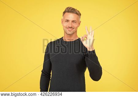 Handsome Man Wear Black And Show Ok Gesture. Male Fashion And Beauty. Guy Looking Stylish And Trendy