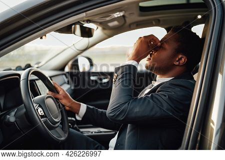 Exhausted African Businessperson Sitting Inside Of Car Holding Wheel.