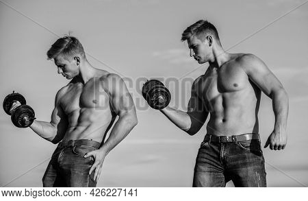Sporty Muscular Guys With Barbell And Dumbbells. Twins Training Together. Developing Muscular Streng