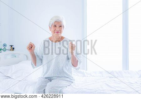 Senior Woman Sittng In Bed At Hospital Ward. Medicine, Health Care And People Concept.