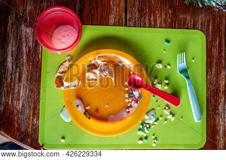 Mess Left At The Kitchen Table After A Toddler Finished. Plastic Fork, Cup And Plate Strewn With Dri