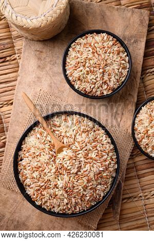 Organic Thai Highland Brown Rice Grain In A Bowl With Wooden Spoon (cargo Rice, Loonzain Rice Or Hus