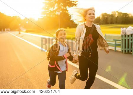 Mom And Schoolgirl Of Primary School Holding Hands. The Parent Takes The Child To School. Outdoors,