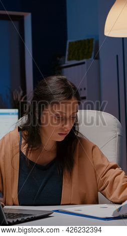 Overworked Businesswoman Analyzing Financial Graphs On Clipboard Comparing With Economic Statistics