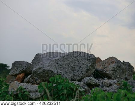 Concrete Waste Material Kept At Grass Field At Sky On Background.