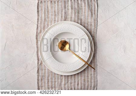 Empty White Plate And Golden Spoon On Napkin. Kitchen Utensils Set On Light Gray Table. Top View Fla