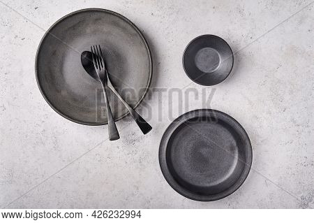 Empty Plates, Gravy Boat, Spoon And Fork. Dark Kitchen Utensils Set On Light Gray Table. Top View Fl