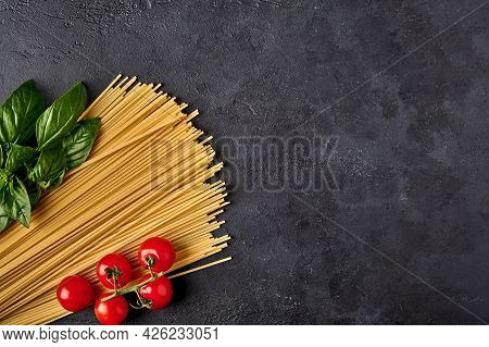 Spaghetti Italian Pasta With Basil Leaves And Tomatoes On Dark Textured Background, Arranged In The