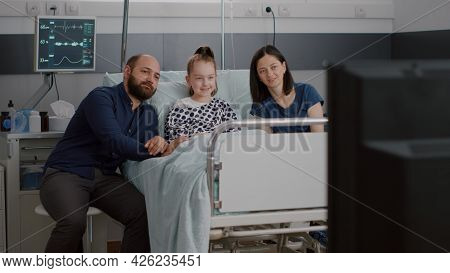 Hospitalized Sick Little Patient Lying In Bed With Family Watching Entertainment Movie On Television