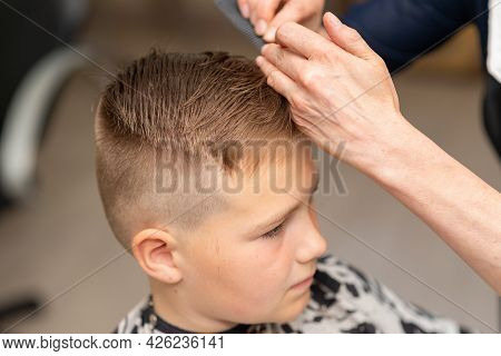 Cute European Boy Getting Hairstyle, Hairdresser Makes A Hairstyle For A Boy.side View.closeup.