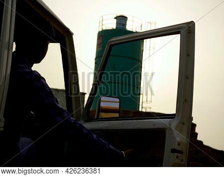 Industrial Vehicle Driver Opening Side Door Around Sky Industrial Background.