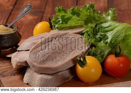 Sliced Beef Tongue Slices On A Platter With Lettuce Leaves, Cherry Tomatoes And Dijon Mustard On A W