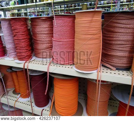 Various Red, Pink And Orange Cord Ropes On Coils On The Shelf.