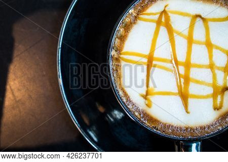 Hot Caramel Macchiato In Black Coffee Cup On Wooden Table Background. Top View