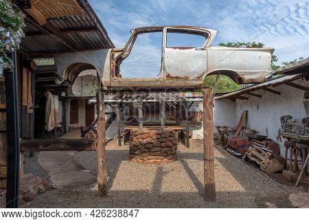 Livingstone, Zambia-november 23, 2017: Jacked Up Rusty Wrecked Car In A Backyard In Livingstone, Zam