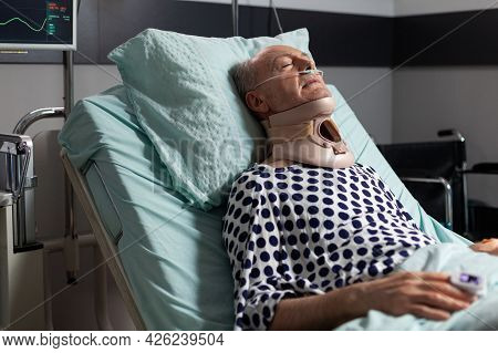 Elderly Man Laying In Hospital Room Bed Wearing Cerival Collar, With Iv Drip. Oxygen Mask Helping Pa