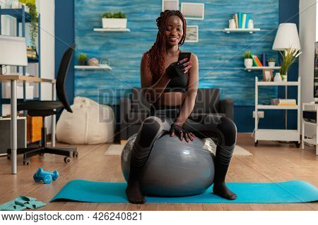 Active Athletic Black Woman Chatting On Smartphone Sitting On Swiss Ball In Home Living Room, After