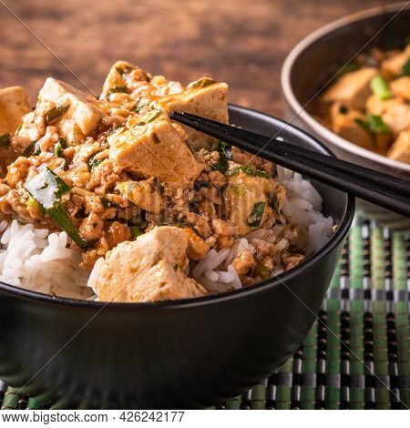 Mapo Tofu With Rice In A Bowl Close-up, Rustic Background, Chopsticks
