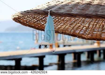 Protective Face Masks Hanging On Wicker Parasol On Sea And Pier Background. Safety On A Beach During