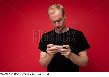 Photo Of Handsome Concentrated Upset Dissatisfied Young Blonde Man Isolated Over Red Background Wall