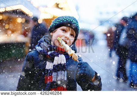 Little Cute Kid Boy Eating White Chocolate Covered Fruits On Skewer On Traditional German Christmas