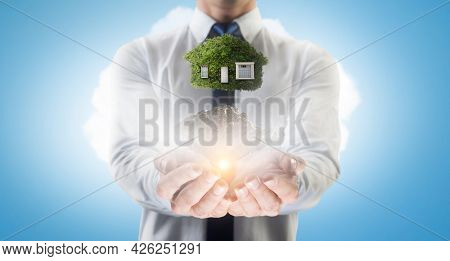 Hand holding green house . Mixed media