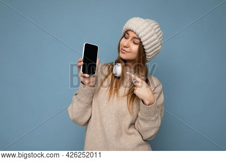 Photo Of Attractive Positive Joyful Young Dark Blonde Woman Wearing Beige Stylish Sweater And Knitte