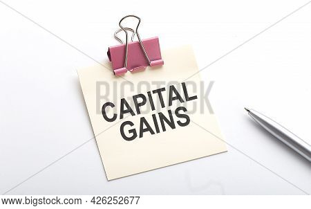 Capital Gains Text On Sticker With Pen On White Background